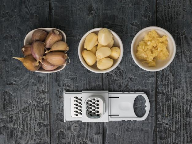皮をむき、皮をむき、すりおろしたにんにくとおろし金を木製のテーブルに。キッチンに人気のスパイス。