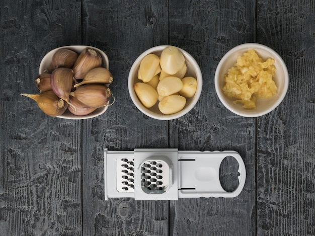 Unpeeled, peeled and grated garlic and grater on a wooden table. a popular spice for the kitchen.