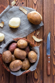 Unpeeled and peeled potatoes in a basket and a knife on a wooden