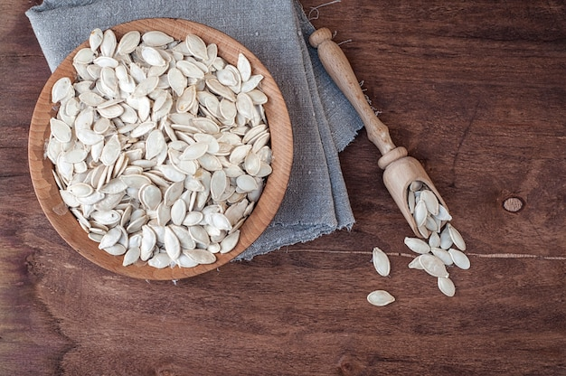 Unpeeled pumpkin seeds in a wooden bowl