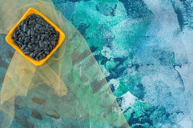 Semi di girasole non pelati in una ciotola su tulle, sul tavolo blu.
