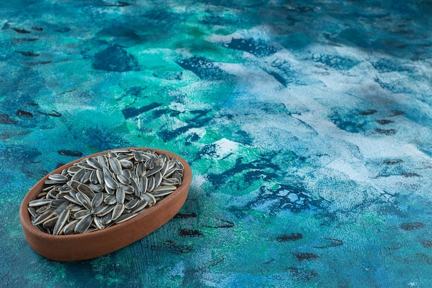 大理石の粘土ボウルに皮をむいていないヒマワリの種。