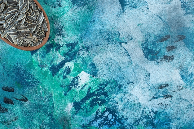 大理石のテーブルの上にある粘土のボウルにある皮をむいていないヒマワリの種。