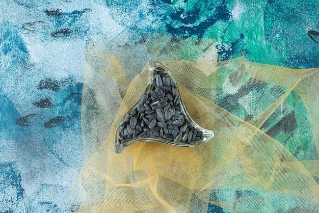 Неочищенные семечки в стеклянной миске на тюле, на синем столе.