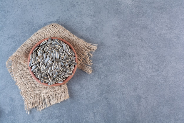 大理石の表面のテクスチャ、粘土プレートの皮をむいていないヒマワリの種