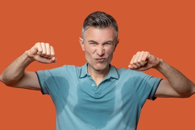 不快なケース。オレンジ色の背景に手を上げて濡れた青いtシャツにしかめっ面で不機嫌な若い大人の男