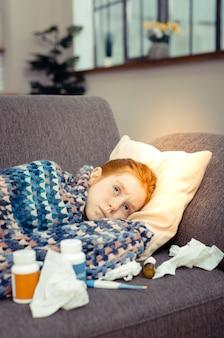 不快な病気。インフルエンザに苦しんでいる間ソファで休んでいる悲しい元気のない女の子