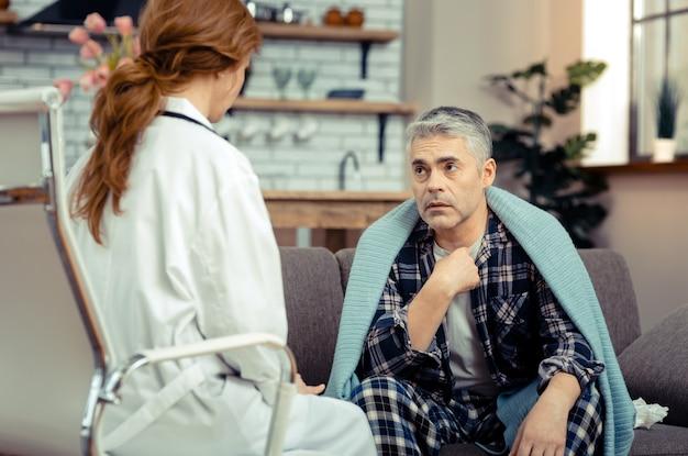 不快な病気。医者と彼の病気について話している間彼の喉を指している悲しい元気のない男