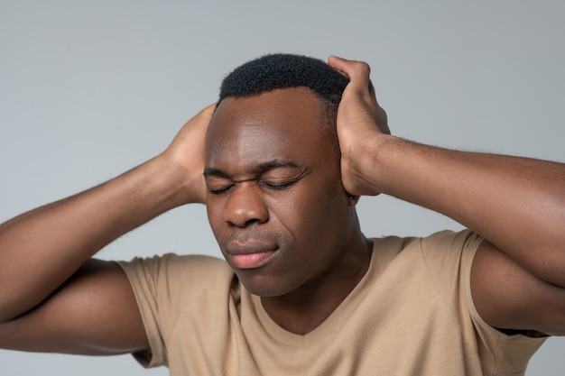 Unpleasant sensation. close-up photo of african american man with closed eyes covering ears with hands on light background