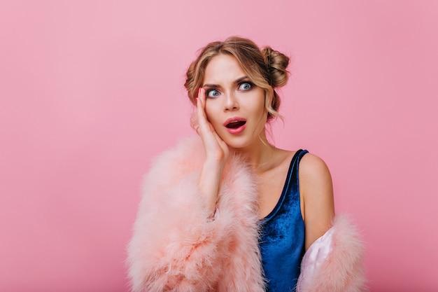 ふわふわのコートとピンクの背景の前に立っているよそ見青いボディースーツの不愉快な驚きの女の子。スタイリッシュなメイクとショックを受けた顔の表情が頬に触れる魅力的な若い女性