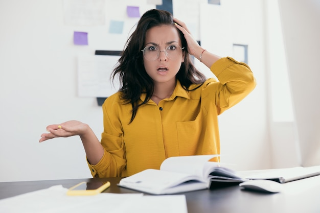 Unpleasantly surprised woman freelancer holding head