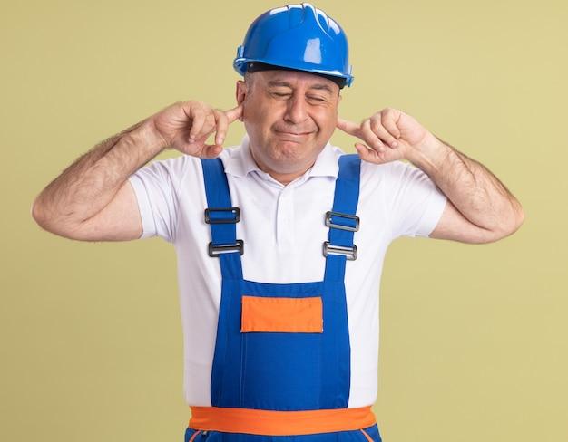 Uomo adulto dispiaciuto del costruttore in uniforme blocca le orecchie con le dita isolate sulla parete verde oliva