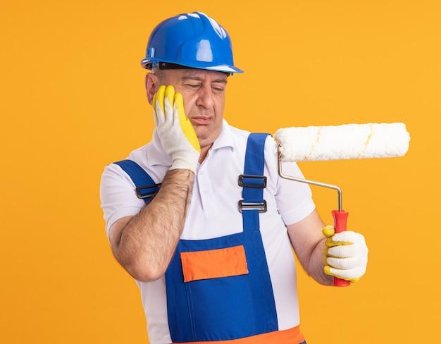 Uomo adulto dispiaciuto del costruttore in uniforme che indossa guanti protettivi mette la mano sul viso e guarda la spazzola a rullo isolata sulla parete arancione