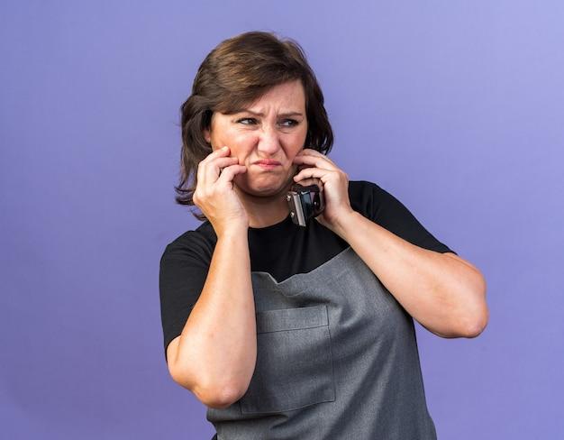 バリカンを持って顔に手を置き、コピースペースで紫色の背景に分離された側を見て制服を着た不機嫌な大人の白人女性理髪師
