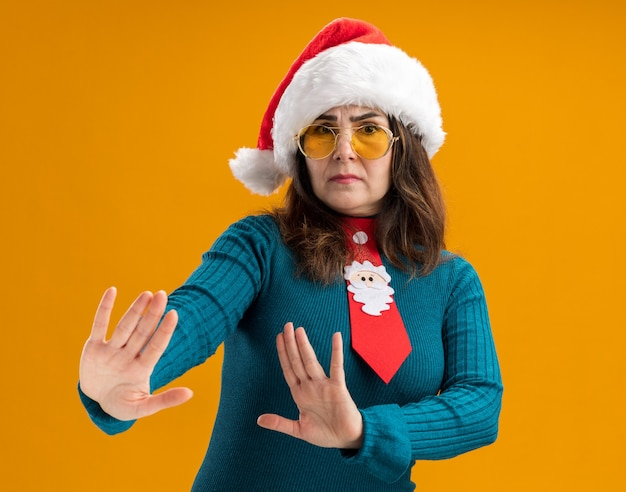 Unpleased adult caucasian woman in sun glasses with santa hat and santa tie holds hands open gesturing no sign isolated on orange background with copy space