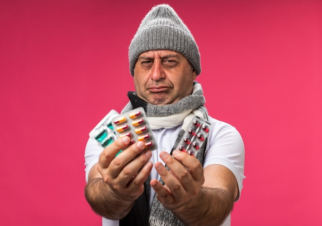Unpleased adult ill caucasian man with scarf around neck wearing winter hat holding different medicine packs isolated on pink wall with copy space