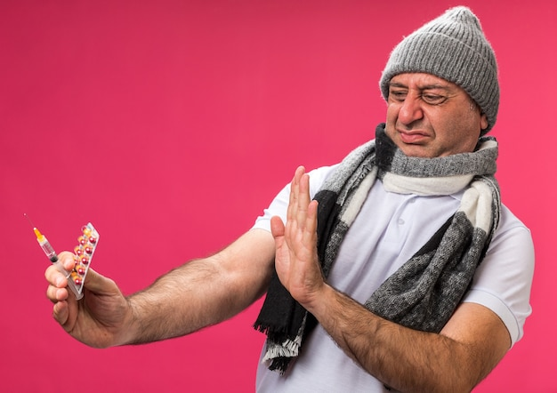 Unpleased adult ill caucasian man with scarf around neck wearing winter hat holding and looking at syringe and medicine blister pack isolated on pink wall with copy space
