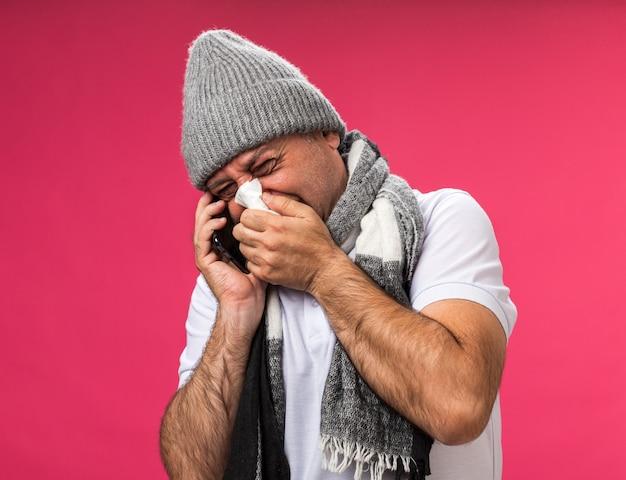 冬の帽子をかぶって首の周りにスカーフを持つ不機嫌な大人の病気の白人男性は、コピースペースでピンクの壁に隔離された電話で話しているナプキンで鼻を拭きます