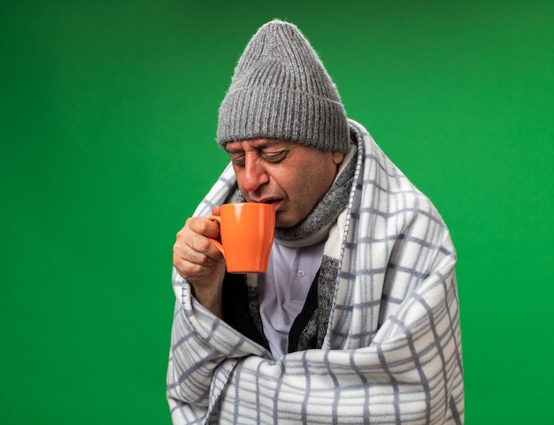 Unpleased adult ill caucasian man with scarf around neck wearing winter hat wrapped in plaid holding and looking at cup isolated on green wall with copy space