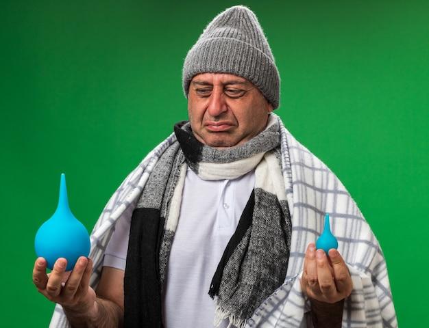 Scontento adulto malato uomo caucasico con sciarpa intorno al collo indossando cappello invernale avvolto in plaid tenendo e guardando clisteri isolato sulla parete verde con spazio di copia
