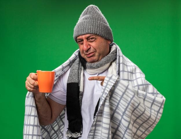 Uomo caucasico malato adulto dispiaciuto con sciarpa intorno al collo che indossa cappello invernale avvolto in plaid tenendo e indicando la tazza isolata sul muro verde con spazio di copia