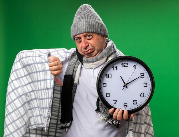 Uomo caucasico malato adulto dispiaciuto con sciarpa intorno al collo che indossa cappello invernale avvolto in plaid pollice verso il basso e tiene l'orologio isolato sulla parete verde con spazio di copia