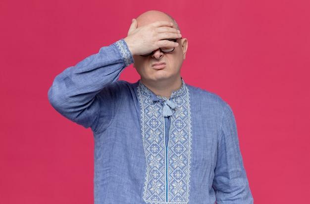 Uomo adulto scontento in camicia blu con gli occhiali che si mette la mano sulla fronte
