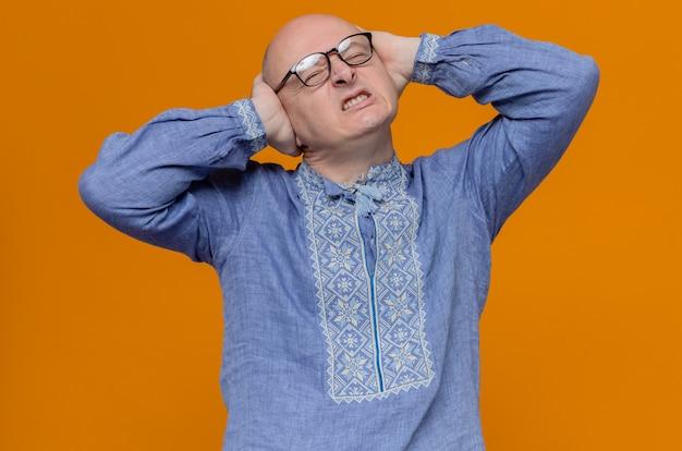 Uomo adulto scontento in camicia blu e con gli occhiali che si chiudono le orecchie con le mani