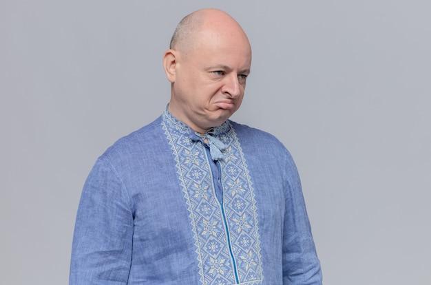 Недовольный взрослый мужчина в синей рубашке, глядя в сторону