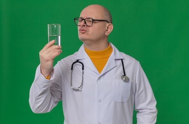 Uomo adulto scontento con gli occhiali in uniforme da medico con uno stetoscopio che tiene in mano e guarda un bicchiere d'acqua
