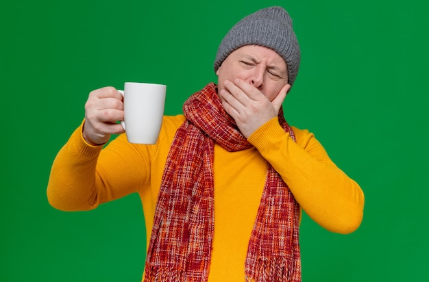 Unpleased adult man with winter hat and scarf around his neck putting hand on his mouth and holding cup