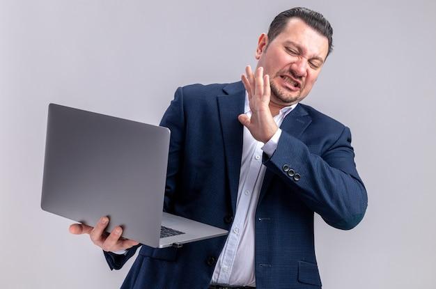 Uomo d'affari slavo adulto scontento che tiene e guarda il laptop