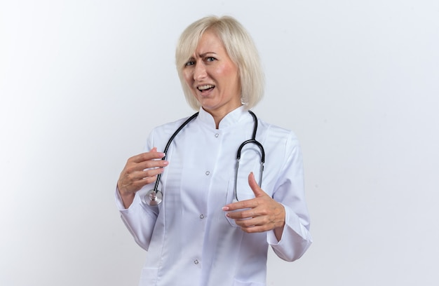 コピースペースで白い背景に分離されたカメラを見て聴診器で医療ローブの不機嫌な大人のスラブ女性医師