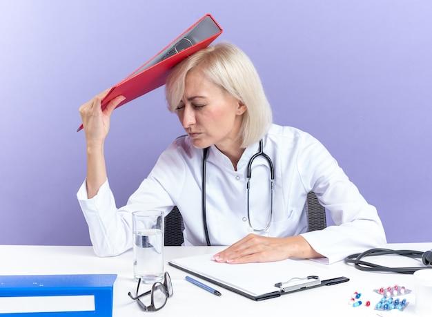 コピースペースと紫色の背景で隔離の頭にファイルフォルダを保持しているオフィスツールと机に座っている聴診器と医療ローブの不機嫌な大人のスラブ女性医師