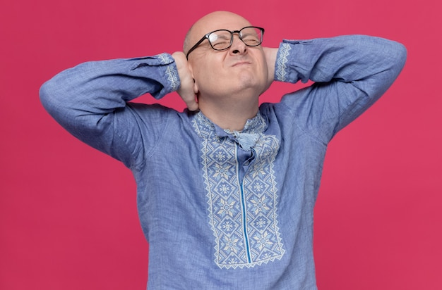 Uomo slavo adulto scontento in camicia blu che indossa occhiali ottici chiudendo le orecchie con le mani