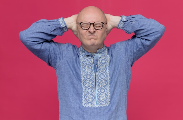 Unpleased adult slavic man in blue shirt wearing optical glasses holding head standing with closed eyes