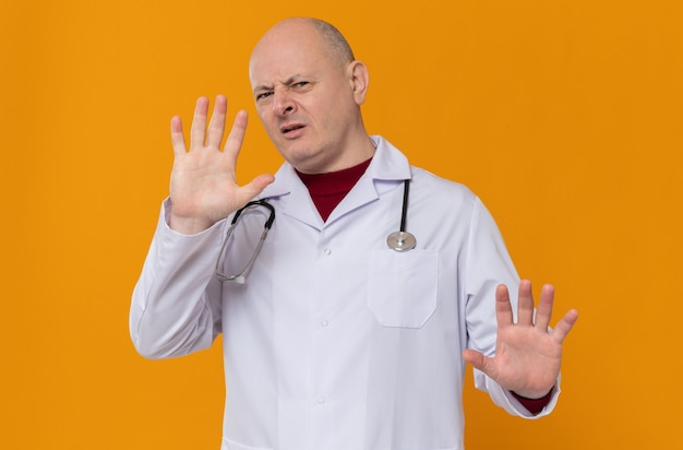 Unpleased adult slavic man in doctor uniform with stethoscope keeping hands open gesturing stop sign