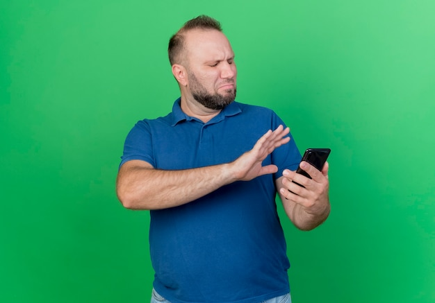 Недовольный взрослый славянский мужчина держит мобильный телефон и не делает жест рукой, изолированной на зеленой стене с копией пространства
