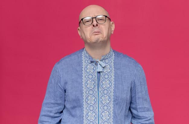 Недовольный взрослый славянский мужчина в синей рубашке в оптических очках смотрит вперед