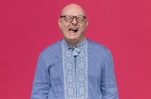 Недовольный взрослый славянский мужчина в синей рубашке в оптических очках стоит с закрытыми глазами