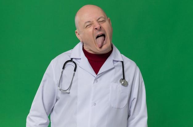 혀를 내밀고 청진기를 들고 의사 유니폼을 입은 불쾌한 성인 슬라브 남자