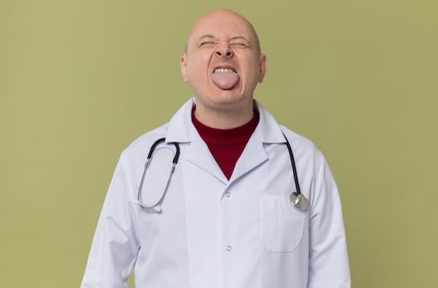聴診器を持った医者の制服を着た不機嫌な大人のスラブ人が目を閉じて立っている彼の舌を突き出します