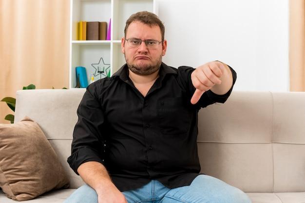 Недовольный взрослый славянский мужчина в оптических очках сидит на кресле большими пальцами вниз в гостиной
