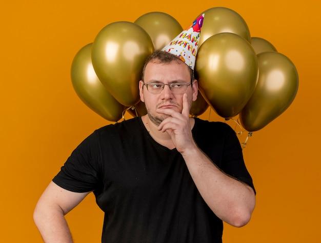생일 모자를 쓰고 광학 안경을 쓴 불쾌한 성인 슬라브 남자가 옆을 바라 보는 얼굴에 손을 대고 헬륨 풍선 앞에 서 있습니다.