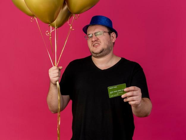 Недовольный взрослый славянский мужчина в оптических очках в синей праздничной шляпе держит гелиевые шары и кредитную карту
