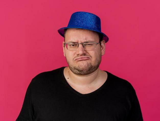 파란색 파티 모자를 쓰고 광학 안경에 불쾌한 성인 슬라브 남자가 카메라를 본다.