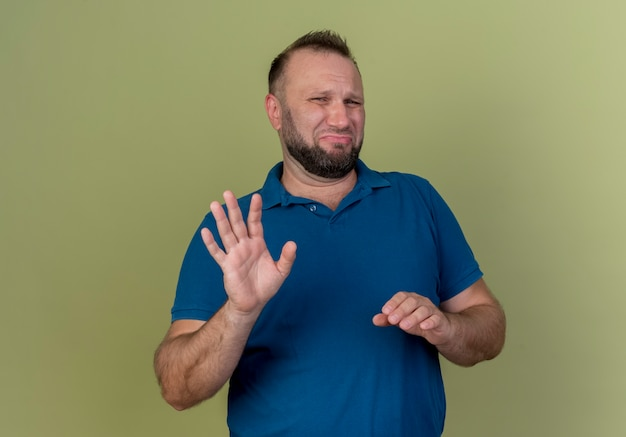 Unpleased adult slavic man keeping hand in air and doing no gesture