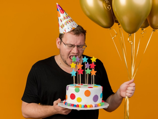 Unpleased adult slavic man in optical glasses wearing birthday cap holds helium balloons and birthday cake