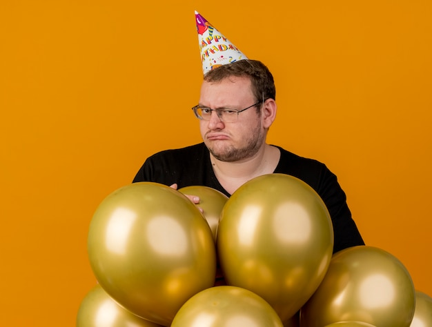 Unpleased adult slavic man in optical glasses wearing birthday cap stands with helium balloons looking at camera