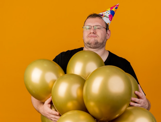 Unpleased adult slavic man in optical glasses wearing birthday cap stands with helium balloons